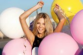 picture of latex woman  - Happy young woman having fun with big colorful latex balloons - JPG