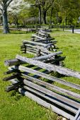 stock photo of split rail fence  - A split rail fence disappearing into the distance by a green field  - JPG
