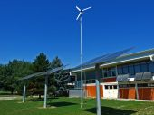 stock photo of wind energy  - Solar and wind collectors in backyard of a school - JPG