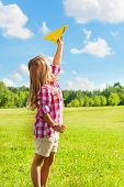 stock photo of 6 year old  - Happy blond 6 years old girl holding yellow paper airplane on bright sunny day - JPG