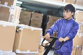 Male chinese worker with fork pallet truck stacker in warehouse loading group of boxes packages