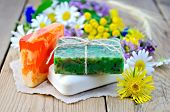 image of tansy  - Three pieces of homemade soap on a piece of paper chamomile flowers tansy elecampane on the background of wooden boards