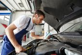 stock photo of car repair shop  - side view of mechanic checking motor oil - JPG