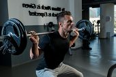 stock photo of squatting  - Young Athlete Doing Barbell Squats In Gym - JPG