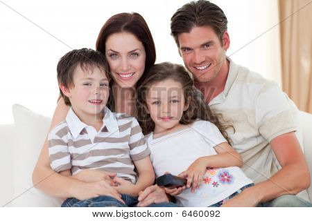 Young Family Watching Tv On The Sofa