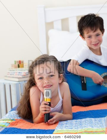 Close-up Of A Cute Girl Girl Singing And Her Brother Playing Guitar