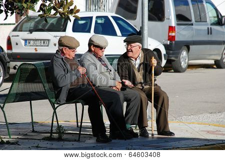 Three Spanish men on a bench.
