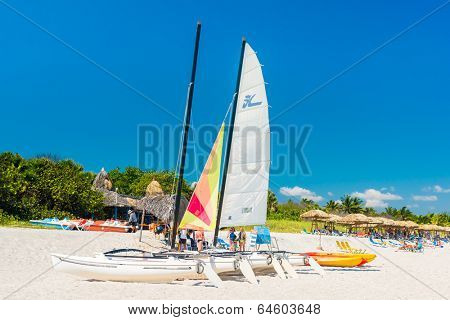 VARADERO,CUBA - APRIL 27,2014: Colorful sailing boats and people resting under thatched umbrellas on a sunny day at the beach