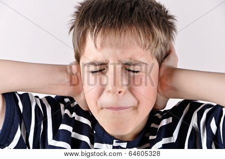 Young boy covering his ears with hands