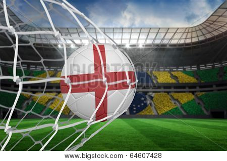 Football in england colours at back of net against large football stadium with brasilian fans