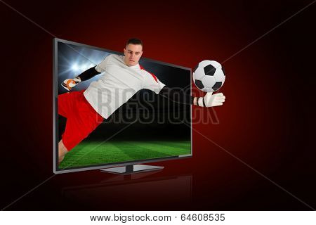 Composite image of fit goal keeper saving goal through tv against football pitch under spotlights