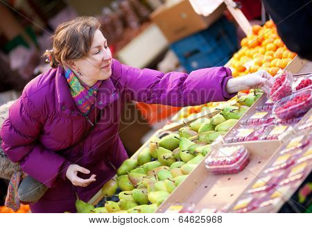 Beautiful Girl In Bright Clothes Choosing Fruits At Fruit Market
