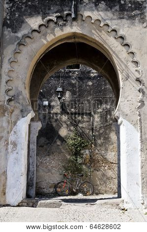 Ancient arch - entrance to Casbah, Tangier with bicycle