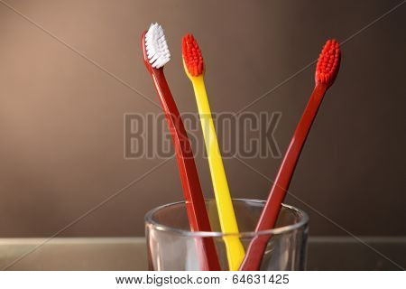 Toothbrushes in glass on brown background