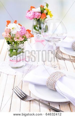 Beautiful table setting with spring flowers in jar close-up