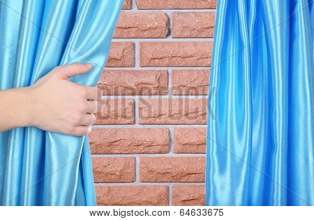 Hand opening curtain on wall background