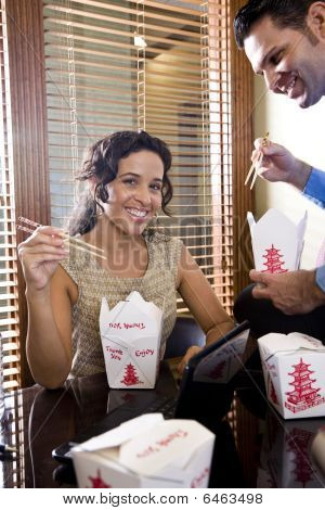 Co-workers in office eating Chinese takeout food