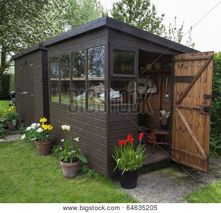 Garden Shed Exterior with Door Open, Tools, Flowers, and Plant Pots.