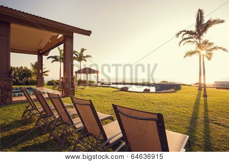 Beautiful Home Exterior Patio Deck and Lounge Chairs with Sunset View on Lawn