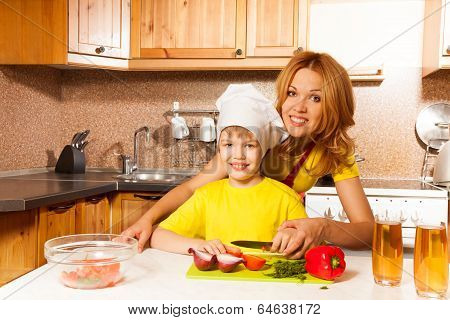 Happy boy using toque cuts vegetables with mother