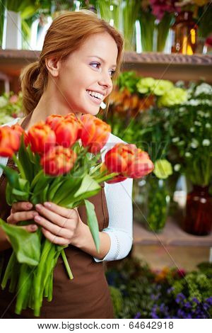 Portrait of young female florist with bunch of fresh tulips