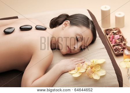 health and beauty, resort and relaxation concept - asian woman in spa salon getting massage with hot stones