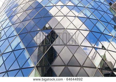 LONDON, UK - APRIL 24, 2014: Gherkin building glass windows texture reflects the sky. The modern gla