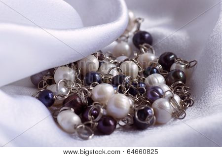 Beautiful jewelry pearl on the background of silk
