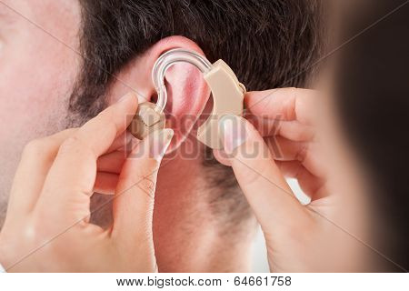 Person Adjusting Hearing Aid