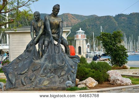 MARMARIS, TURKEY - APRIL 2, 2014: Monument to fishermen on the embankment. The monument reminds that few decades ago the modern resort was a sleepy fishing village