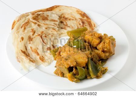 Aloo capsicum, potato and bell pepper vegetarian curry, served with paratha fried flatbread in the traditional way.