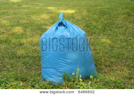 garbage in plastic bag on grass