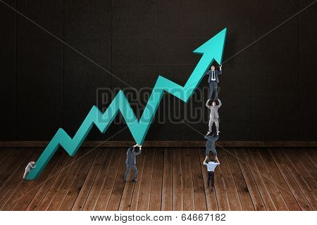 Business team holding up arrow against dark room with floorboards