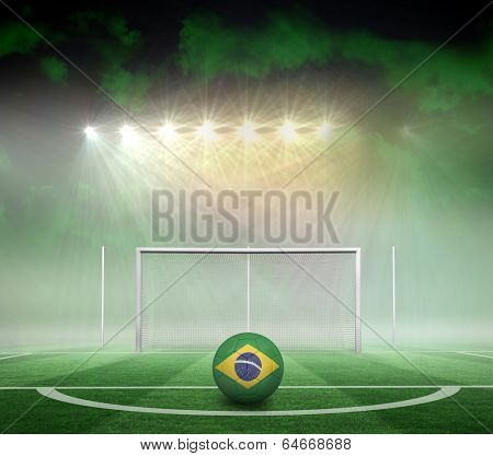 Football in brasil colours against football pitch under spotlights