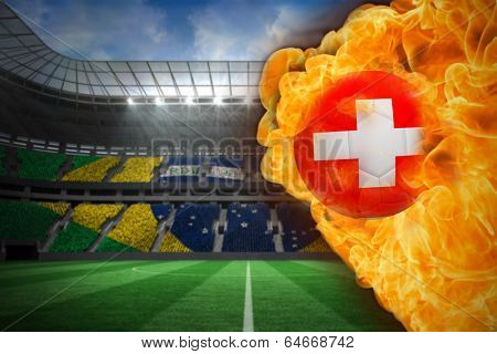 Composite image of fire surrounding switzerland flag football against large football stadium with brasilian fans