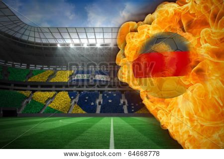 Composite image of fire surrounding germany flag football against large football stadium with brasilian fans