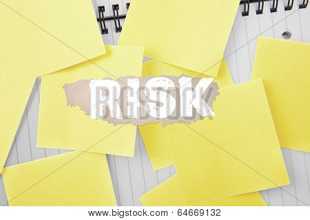 The word risk against sticky notes strewn over notepad