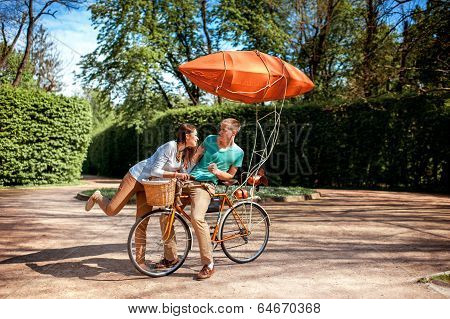 Lovely Young Couple Having Fun With The Bicycle With Red Dirigible In The Park In The Summer