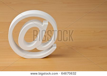 the e-mail logo in white on a wooden plate