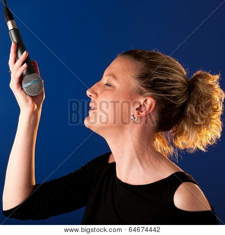 Woman Singer On Bluue Background With Microphone