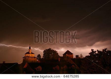 Lightning in a storm in old medival city with castle and a chapel (Kamnik, Slovenia)
