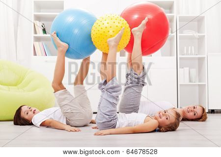 Happy and healthy family exercising at home using large gymnastic balls