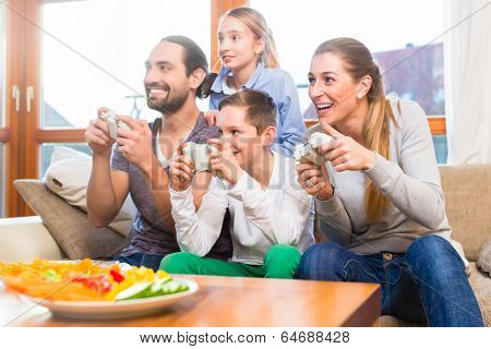 Family having leisure time together and playing with video game console
