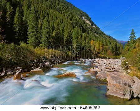 Stormy and frothy mountain stream. Cascades of cold water at the source of the famous Krimml waterfalls. Pastoral in the Alpine mountain valley in Austria