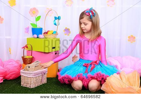 Beautiful small girl in petty skirt with rabbit on decorative background
