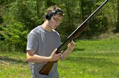 stock photo of shotgun  - A young teenager loading a shotgun getting ready to practice shooting targets - JPG