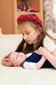 stock photo of emo-boy  - Older sister hugging baby lying on the bed - JPG