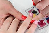 stock photo of finger-painting  - Finger nail treatment painting flower with brush and lacquer - JPG