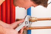 foto of pipe wrench  - Closeup of a handyman using wrench for pipes - JPG