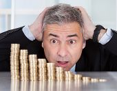 stock photo of descending  - Shocked Mature Businessman Looking At Descending Stack Of Coins